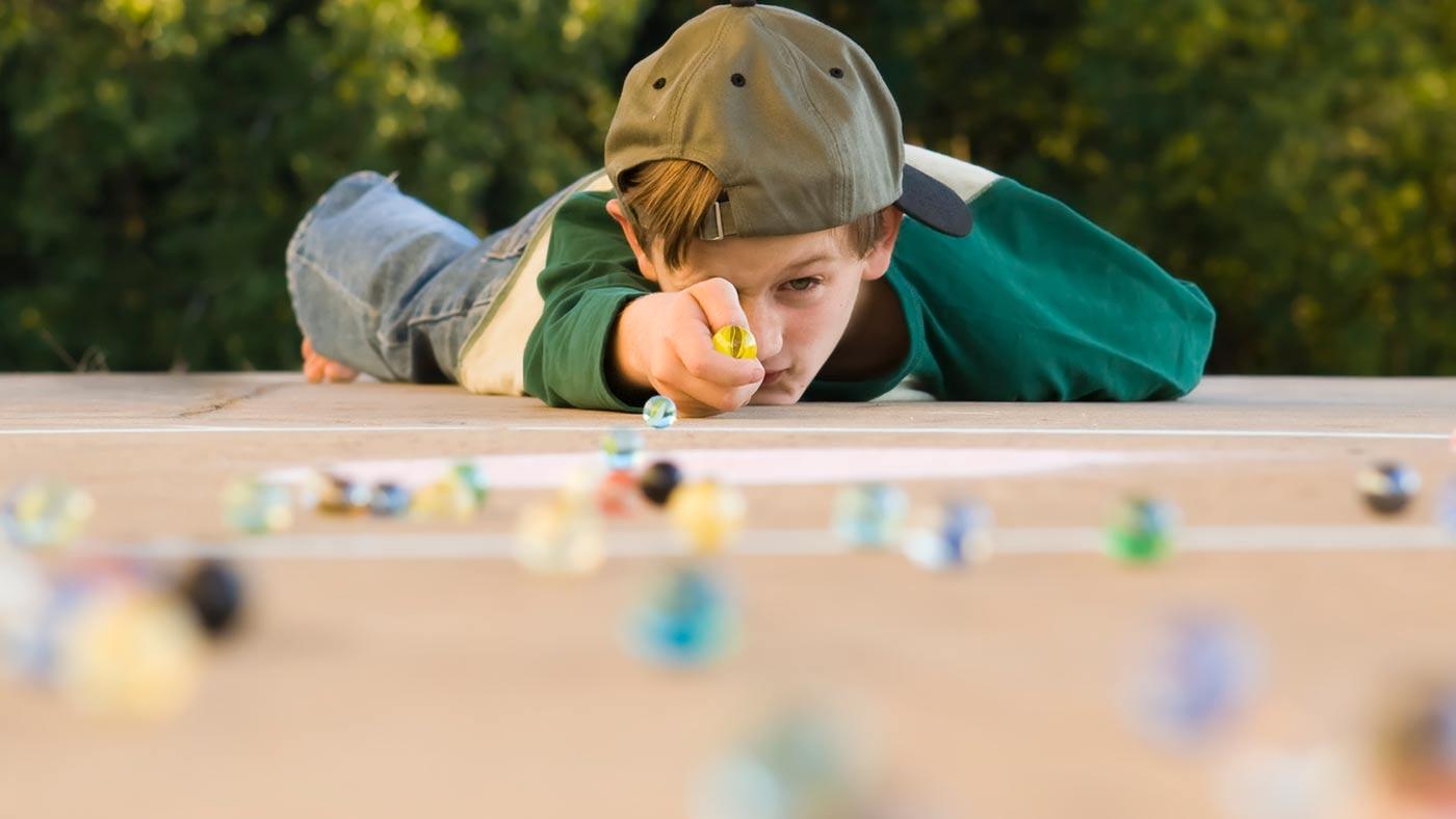 Criança brincando com bolinhas de gude