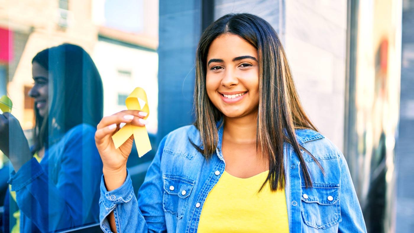 mulher segurando uma fita amarela, em apoio a campanha de prevenção a suicídios