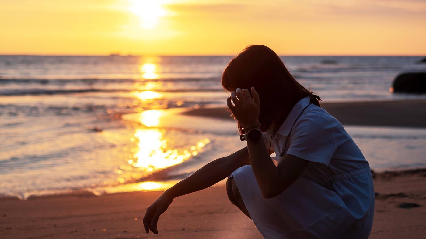 mulher abaixada em praia, com aparência deprimida